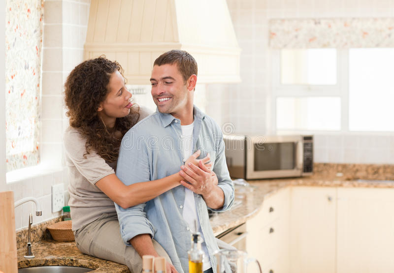 Pares bonitos que abraçam na cozinha fotografia de stock