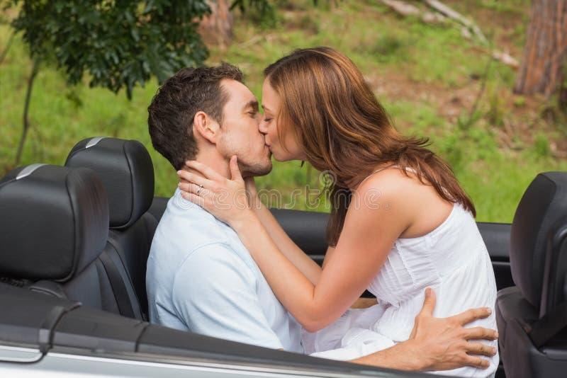 Pares bonitos que beijam no banco traseiro imagem de stock royalty free