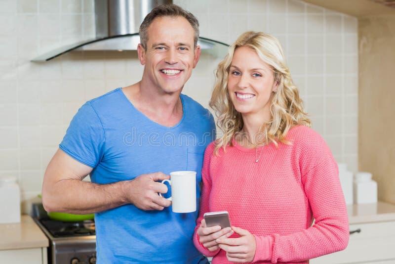 Pares bonitos que comem o café e que olham o smartphone imagem de stock royalty free
