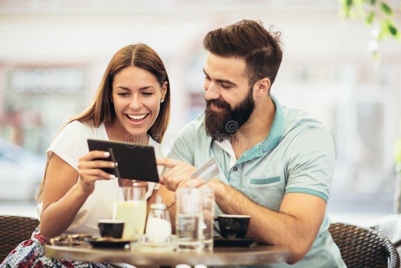 Pares bonitos que comem o café em uma data, usando a tabuleta digital fotografia de stock royalty free