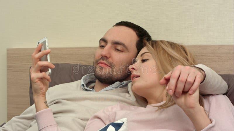 Pares bonitos que encontram-se na cama e no smartphone do uso, tomando a foto do panorama imagem de stock
