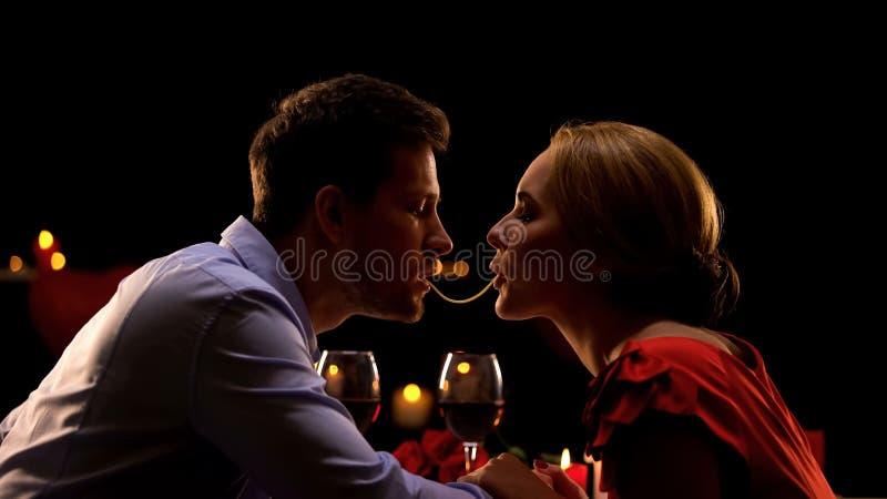 Pares bonitos que fazem os espaguetes beijar na data romântica no restaurante, amor imagem de stock