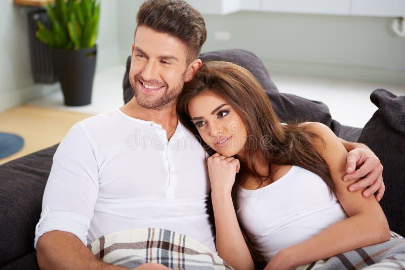 Pares bonitos que relaxam no sofá foto de stock royalty free