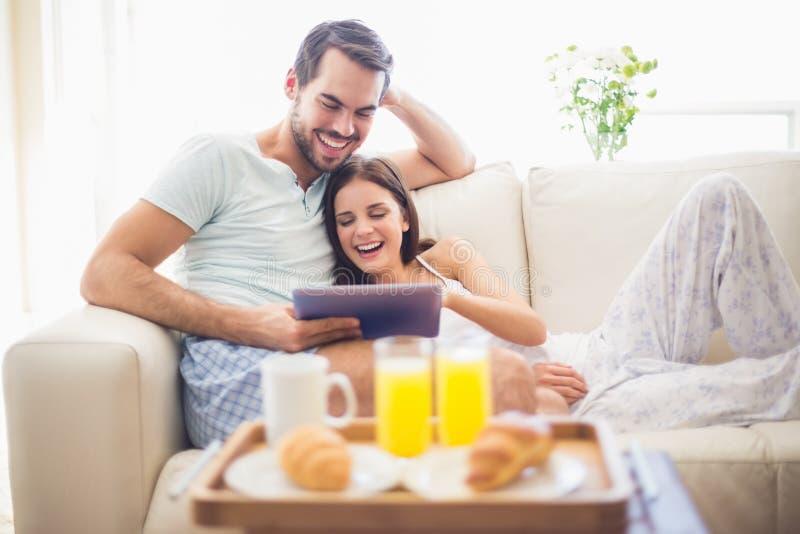 Pares bonitos que relaxam no sofá com a tabuleta no café da manhã fotos de stock