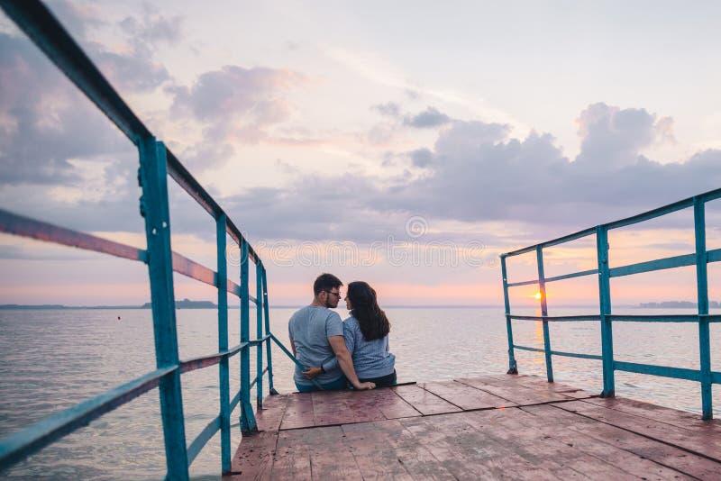 Pares bonitos que sentam-se no cais e que olham no nascer do sol foto de stock royalty free