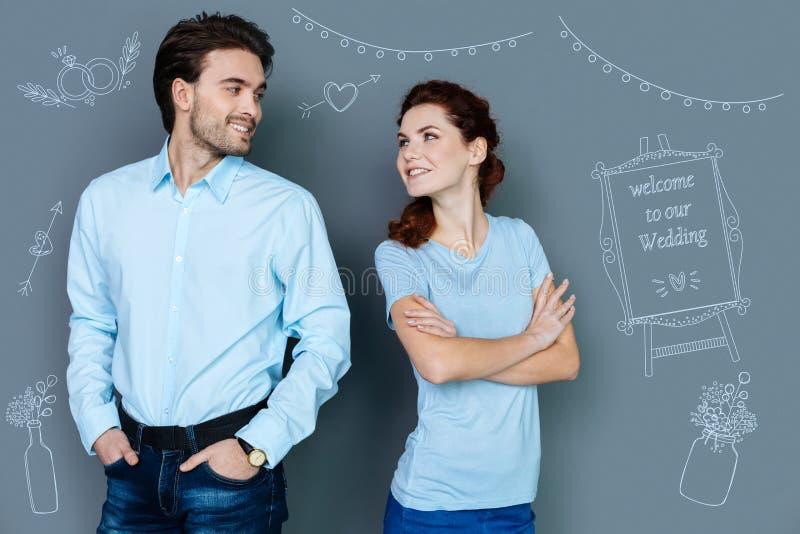 Pares bonitos que sorriem entre si e que esperam seu casamento fotografia de stock royalty free