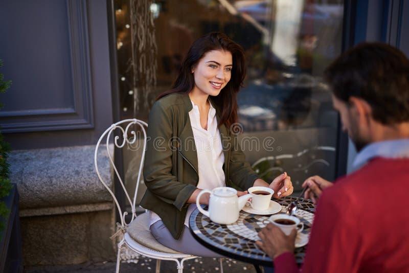 Pares bonitos que têm a reunião romântica no café exterior fotografia de stock royalty free
