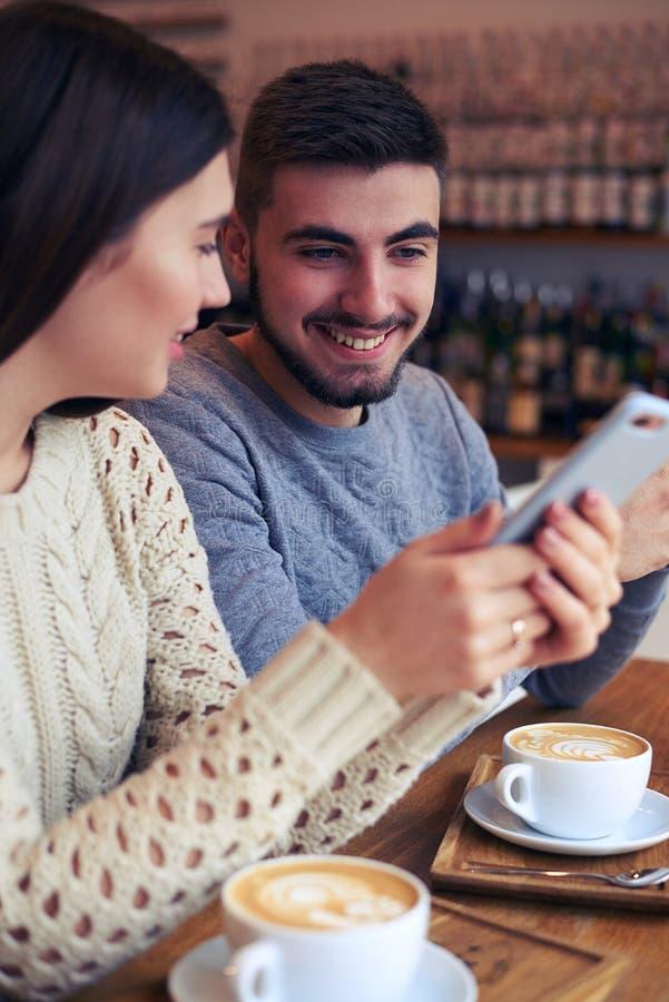 Pares bonitos usando telefones no café imagens de stock