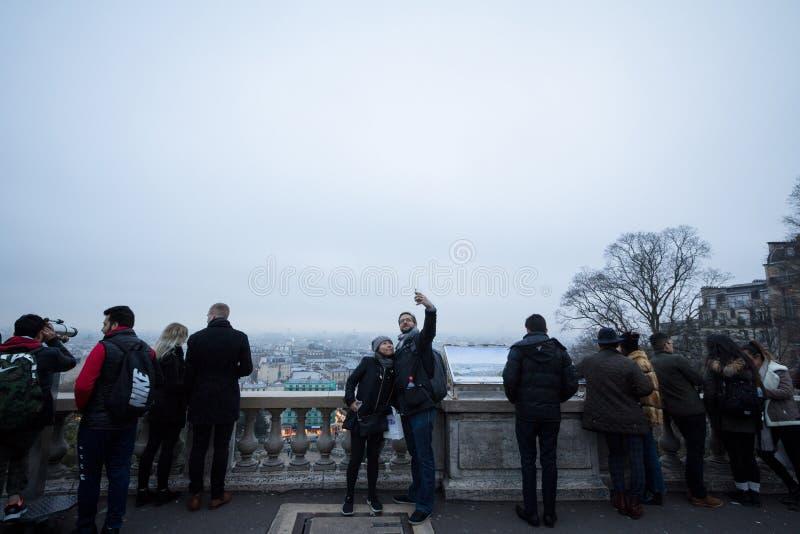 Pares brancos novos que tomam a um selfie dentro o meio de uma multidão do turista no monte de Montmartre foto de stock