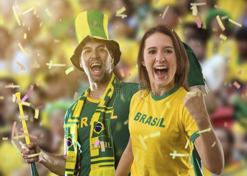 Pares brasileños que celebran en un estadio foto de archivo