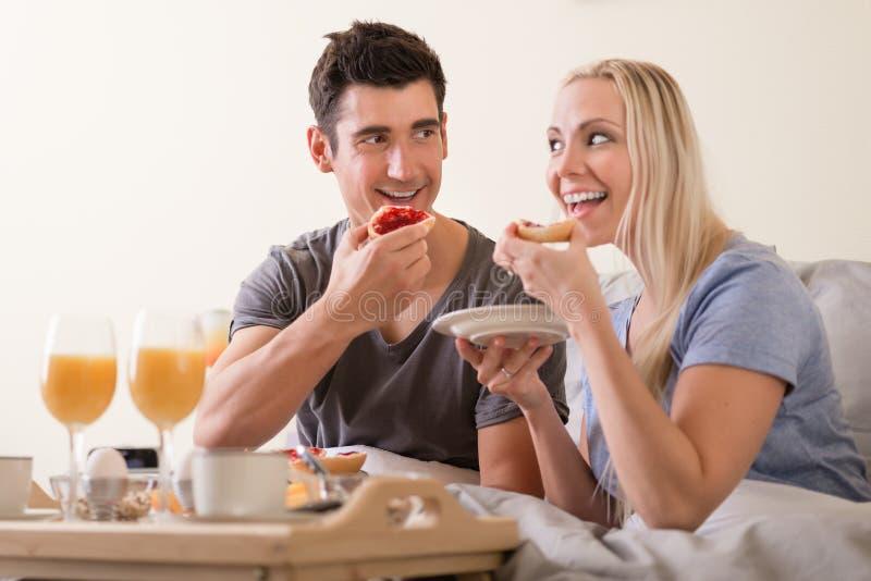 Pares brincalhão felizes que apreciam o café da manhã na cama fotos de stock royalty free