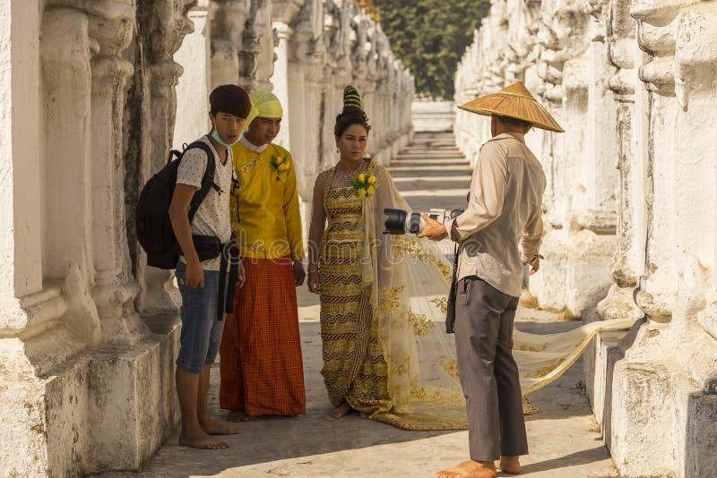 Pares burmese na roupa elegante que está sendo treinada por seu fotógrafo do casamento imagem de stock royalty free
