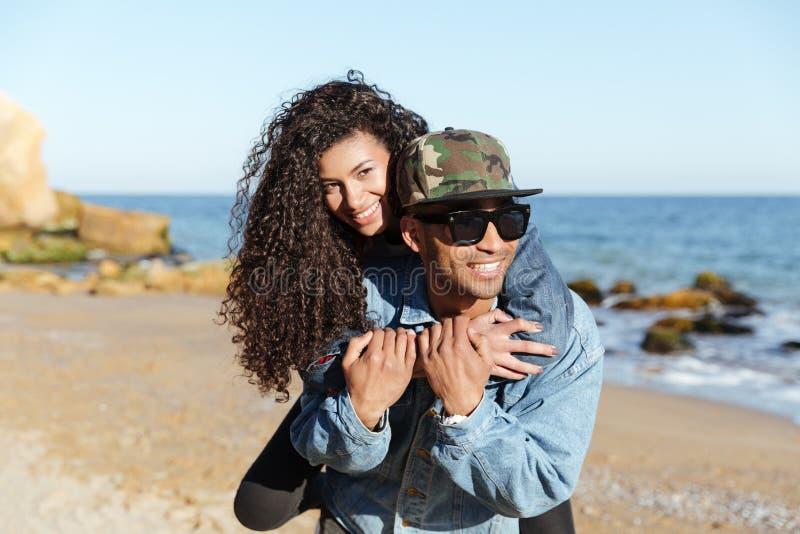 Pares cariñosos africanos felices que caminan al aire libre en la playa fotos de archivo libres de regalías