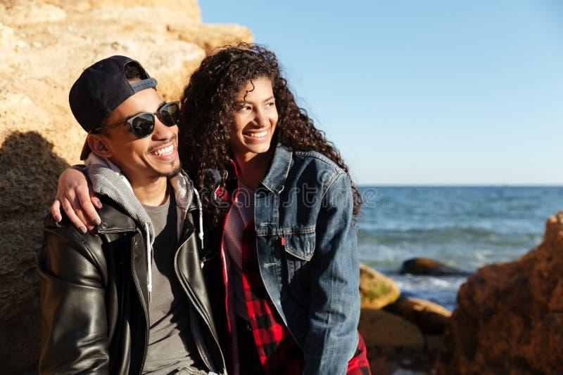 Pares cariñosos africanos felices que caminan al aire libre en la playa imagen de archivo libre de regalías