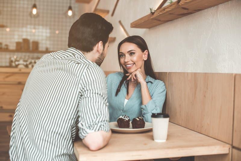 Pares cariñosos alegres que hablan en cafetería fotografía de archivo libre de regalías