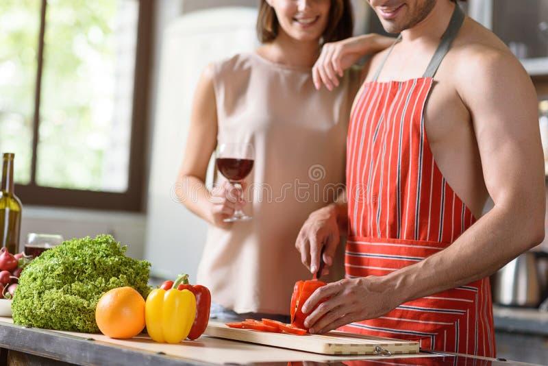 Pares cariñosos alegres que preparan la comida sana imagen de archivo