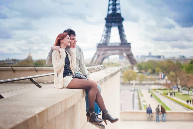 Pares cariñosos cerca de la torre Eiffel en París imagenes de archivo