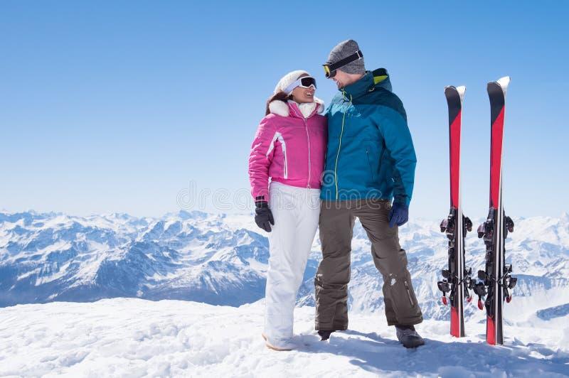 Pares cariñosos con el esquí imagen de archivo libre de regalías
