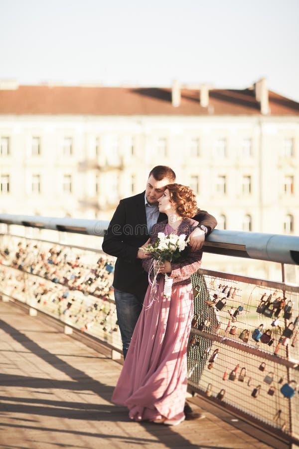 Pares cariñosos elegantes de la boda, novio, novia con el vestido rosado que se besa y que abraza en un puente en la puesta del s imagenes de archivo