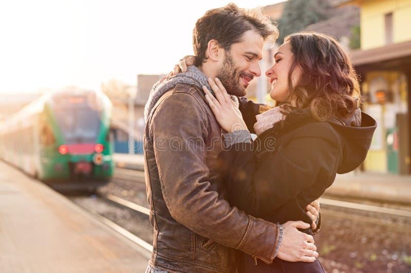 Pares cariñosos en la estación de tren imagenes de archivo