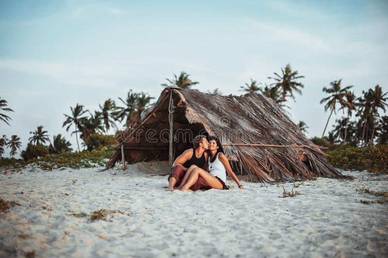 Pares cariñosos en la playa cerca de la choza imagenes de archivo