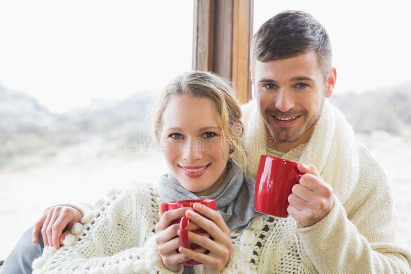 Pares cariñosos en ropa del invierno con las tazas de café contra ventana imagen de archivo