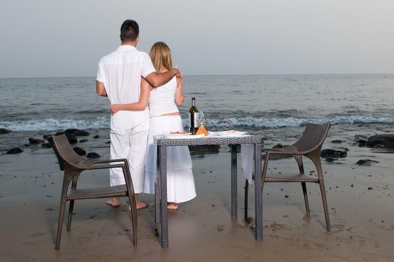 Pares cariñosos en una cena romántica en la playa foto de archivo