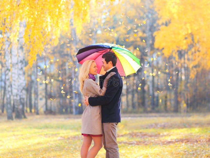 Pares cariñosos felices con el paraguas colorido en día soleado caliente sobre las hojas de vuelo amarillas imagen de archivo