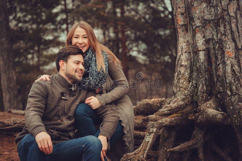Pares cariñosos felices en el paseo acogedor en bosque del otoño foto de archivo