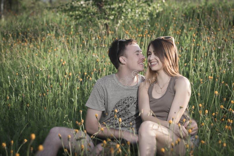 Pares cariñosos felices en naturaleza entre las flores amarillas fotografía de archivo