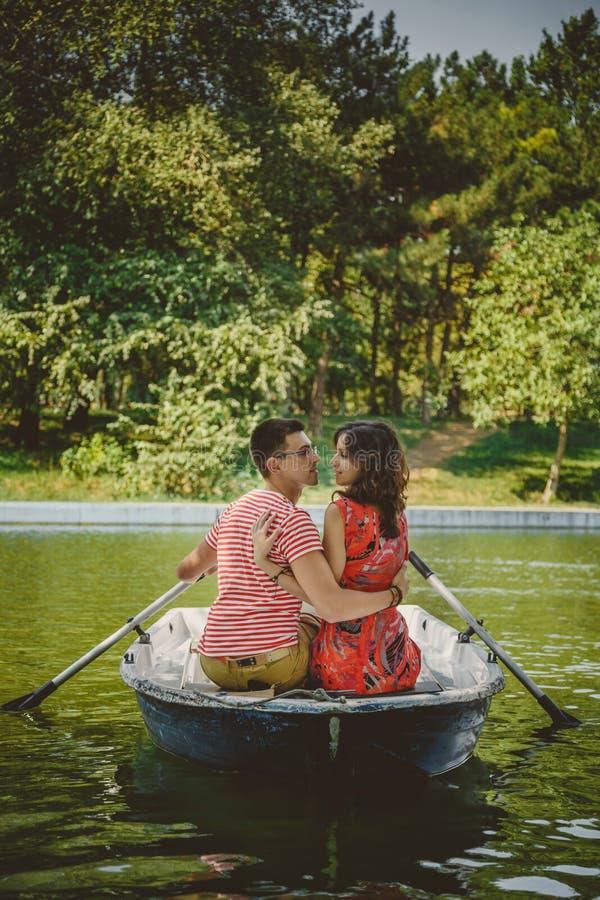 Pares cariñosos felices hermosos jovenes que reman un bote pequeño en un lago Una fecha de la diversión en naturaleza Pares que a foto de archivo