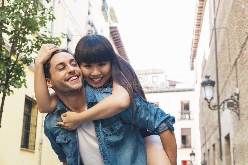 Pares cariñosos felices Hombre joven feliz que lleva a cuestas a su novia fotografía de archivo