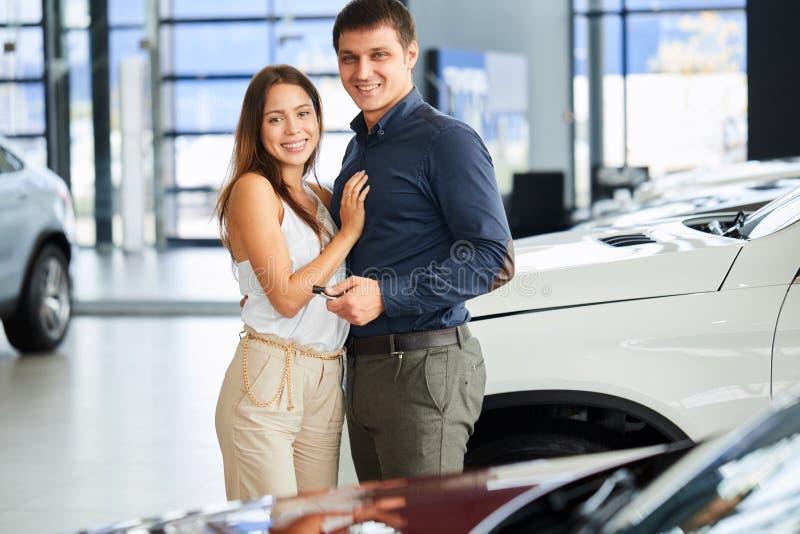 Pares cariñosos felices que abrazan cerca de su nuevo coche de lujo en la representación fotos de archivo libres de regalías