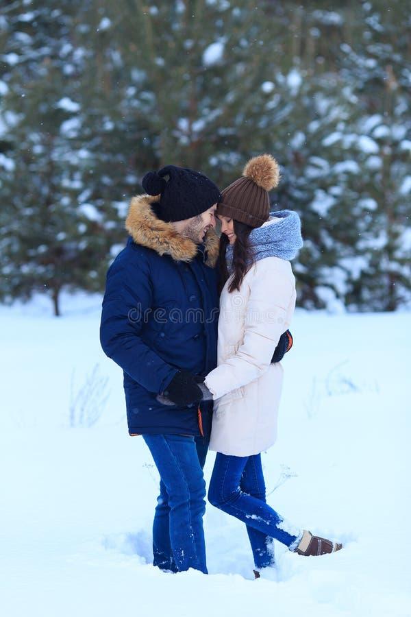 Pares cariñosos felices que caminan en bosque nevoso del invierno foto de archivo libre de regalías