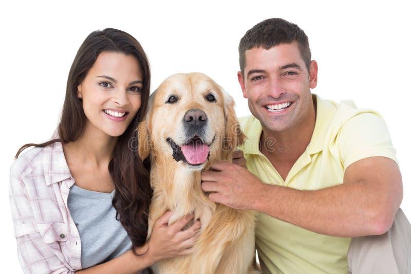 Pares cariñosos felices que frotan ligeramente el perro imagen de archivo