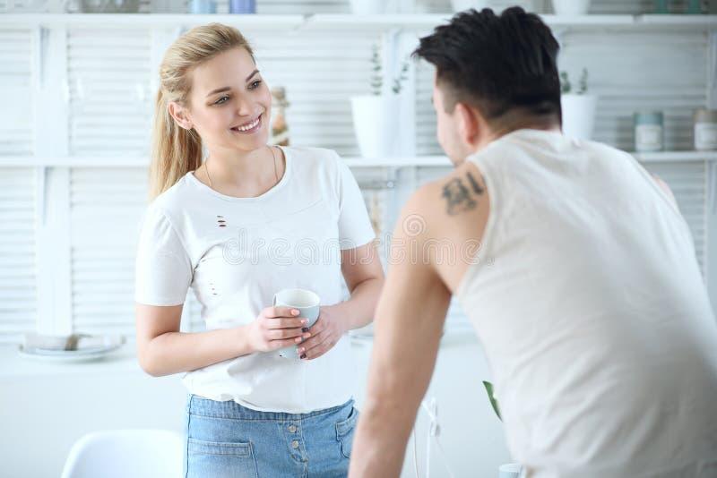 Pares cariñosos hermosos jovenes que se colocan en la cocina enfrente de uno a y que ríen mientras que bebe el café foto de archivo libre de regalías