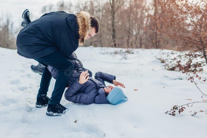 Pares cariñosos hermosos que juegan en el hombre del bosque del invierno que detiene y que empuja a la novia en nieve Gente que s foto de archivo libre de regalías