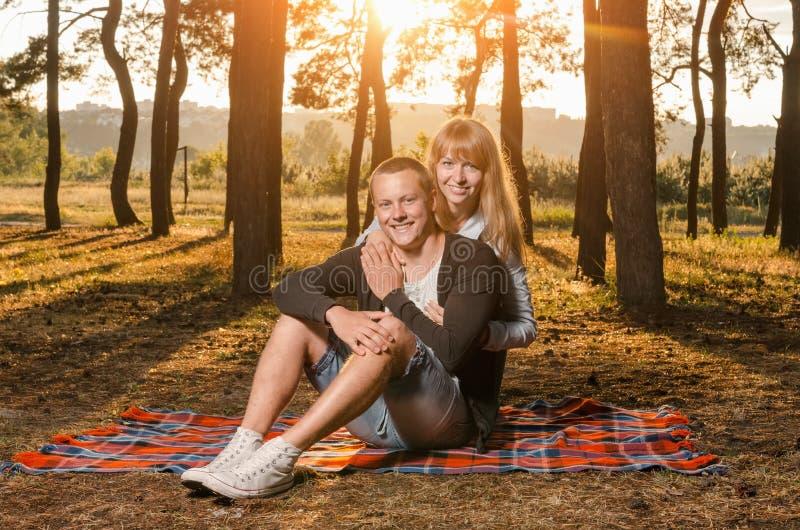 Pares cariñosos jovenes en el parque que se sienta en una manta foto de archivo