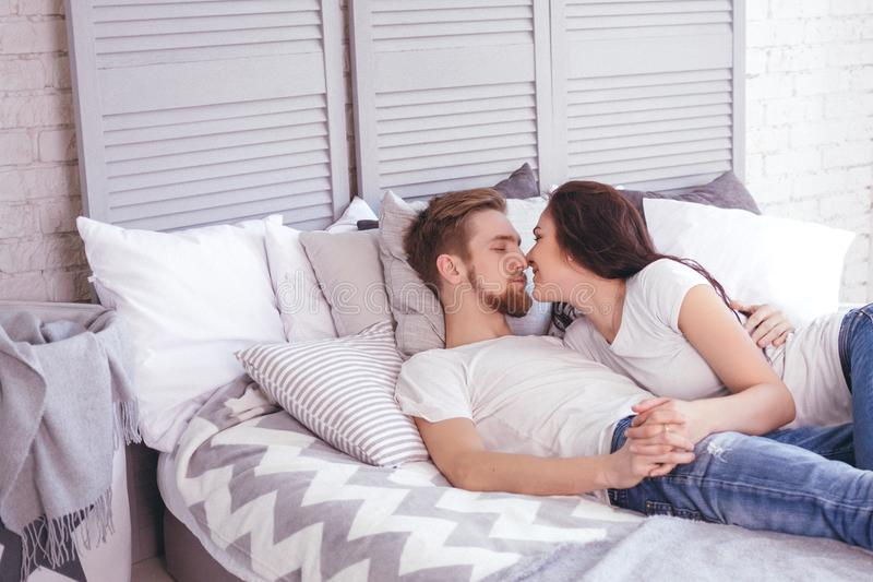 Pares cariñosos jovenes en la cama foto de archivo libre de regalías