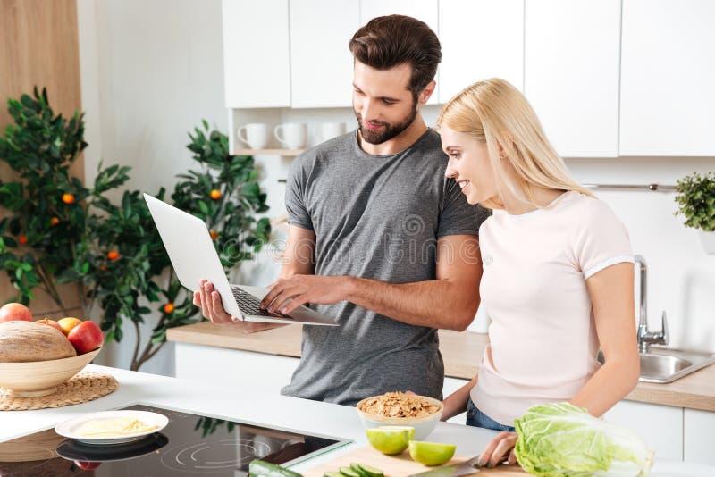 Pares cariñosos jovenes felices que se colocan en la cocina y cocinar fotos de archivo libres de regalías