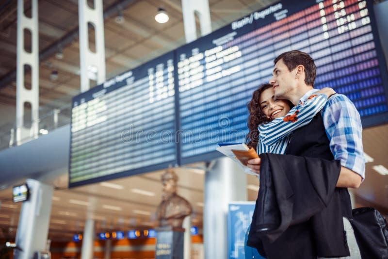 Pares cariñosos jovenes que abrazan en el terminal de aeropuerto fotografía de archivo