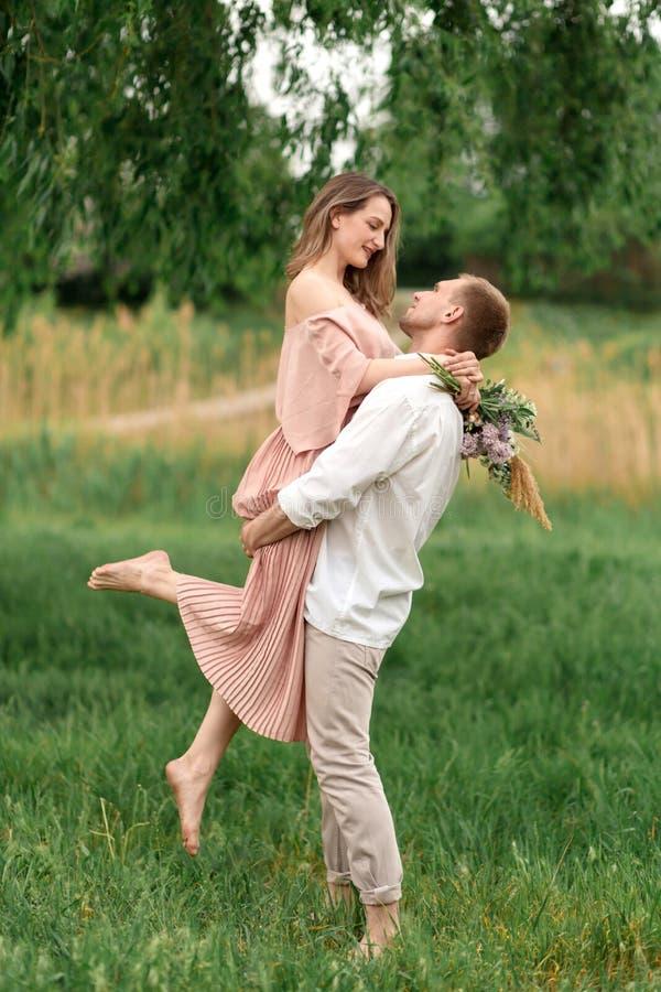 Pares cariñosos jovenes que abrazan y que bailan en la hierba verde en el césped La mujer y el hombre hermosos y felices se tocan foto de archivo libre de regalías