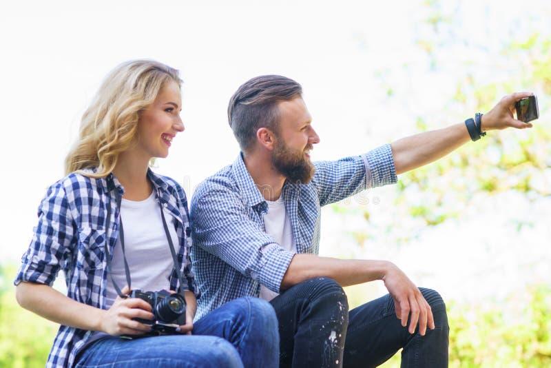 Pares cariñosos jovenes que hacen la foto del selfie al aire libre imagenes de archivo