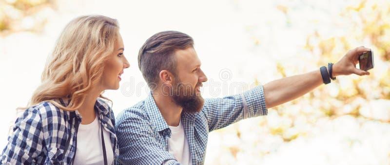 Pares cariñosos jovenes que hacen la foto del selfie en parque del otoño fotos de archivo libres de regalías