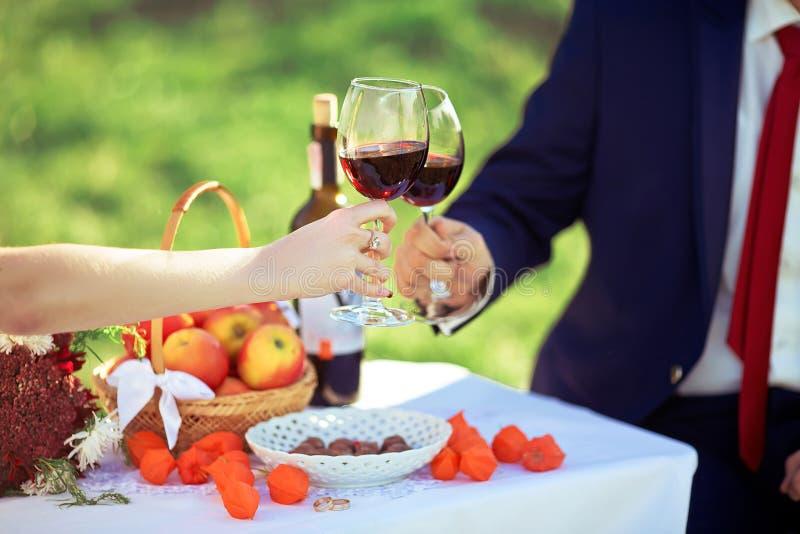 Pares cariñosos que beben el vino rojo de los vidrios transparentes, día de boda, comida campestre al aire libre imágenes de archivo libres de regalías