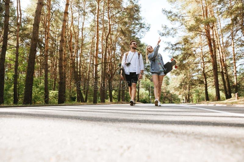 Pares cariñosos que caminan con los monopatines al aire libre foto de archivo libre de regalías