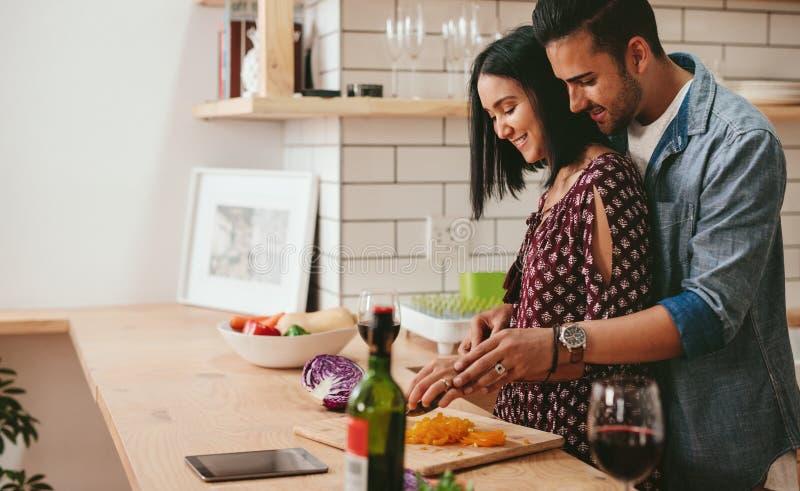 Pares cariñosos que cocinan en cocina en casa fotografía de archivo libre de regalías