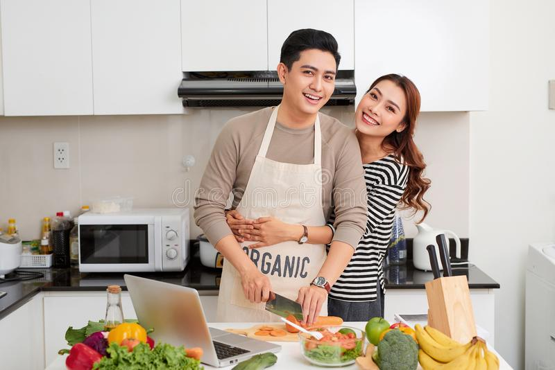 Pares cariñosos que cocinan junto en la cocina en casa fotos de archivo