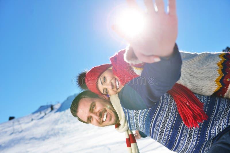 Pares cariñosos que juegan junto en la nieve al aire libre fotografía de archivo