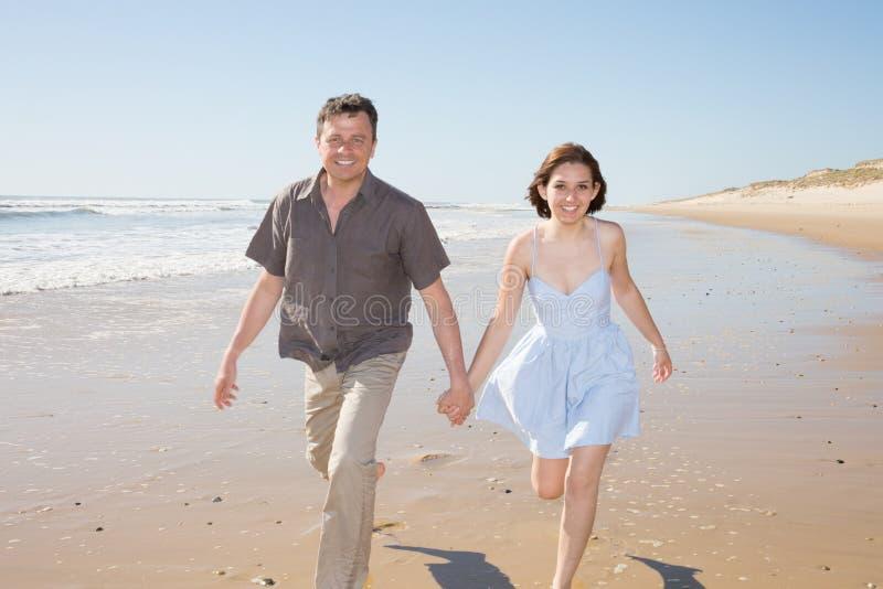 Pares cariñosos que llevan a cabo las manos y que caminan en la playa de la arena con salida del sol hermosa en amor y la liberta foto de archivo